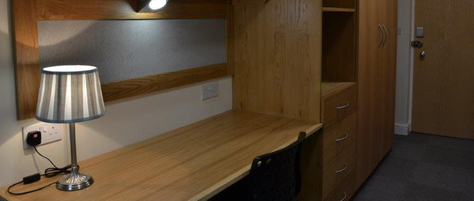 The student accommodation at Longdales Lodge offers desk space, a chair and storage.
